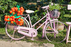 An old pink bike standing on the street Royalty Free Stock Image