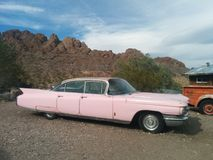 Old, pink Cadillac car in the desert. With mountains and a metal shack in the background, and an orange pickup truck to the side royalty free stock image