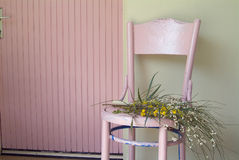 Old pink chair and flowers. In front of green wall and pink door Stock Image