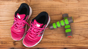 Old pink sneakers with fitness dumbbells on wood background Stock Photo