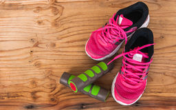 Old pink sneakers with fitness dumbbells on wood background Royalty Free Stock Photos