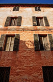 Old pink wall. Old building grunge pink painted with two rows of old wooden windows Royalty Free Stock Image