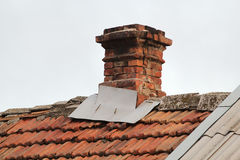Old pipe from the furnace on the roof out shingles, on grey sky Royalty Free Stock Photography