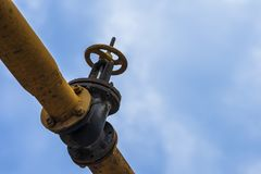 Old pipe with valve, crane mechanism on sky background Stock Photos