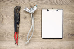 Old pipe wrench and tap with clipboard Stock Photos