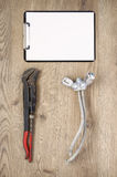 Old pipe wrench and tap with clipboard Royalty Free Stock Photo