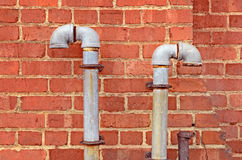 Old Pipes. Rusted pipes against brick wall stock photos