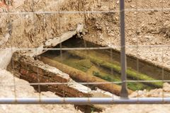 Old pipes in the pit. Rusty water pipes in a pit flooded with water, behind a metal fence stock photography