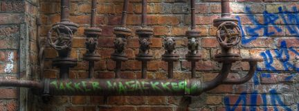 Old pipes with valves on a wall with graffiti Stock Images
