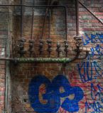 Old pipes with valves on a wall with graffiti Royalty Free Stock Image