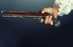 Old pirate pistol. Pirate hand holding ancient pistol. Studio shot. Natural colors and darkness Royalty Free Stock Images