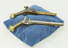 Old pistols. On blue pillow and white background Royalty Free Stock Image