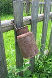 Old pitcher on fence. Old rusty pitcher hung on the fence Royalty Free Stock Images