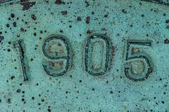 Old pitted metal plaque with numbers and green patina. Macro closeup of copper or brass embossed metal with year 1905 Stock Images