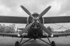 Old plane in black and white colors. An old obsolete aircraft propeller on sky fon Royalty Free Stock Photo