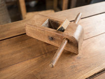 Old plane for wood working. A small asian old plane for wood working placed on a wooden table in a workshop room Stock Images
