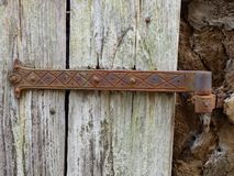 Old plank door with a rusty hinge stock image