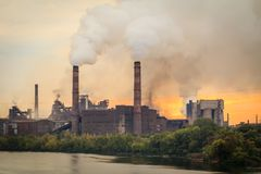 Old plant with smokestacks blowing smoke into the atmosphere stock images