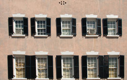 Black Shutters on White Windows on Stucco Building Stock Image