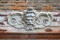 The old plaster head of a man on the facade of a building stock image
