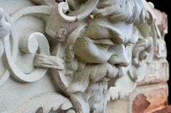 The old plaster head of a man on the facade of a building stock photography