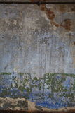 Old plastered brick wall with the remnants of peeling paint different layers and colors. Stock Image