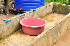 Old plastic basin in cement sink for cleaning Royalty Free Stock Images