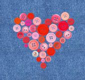 Old plastic buttons in a heart shape over jeans Stock Photos