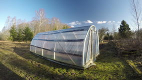 Old plastic greenhouse in spring farm and evening clouds, time lapse 4K stock video footage