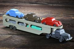 Old plastic model transporter. Carrying colorful cars on wooden background royalty free stock image