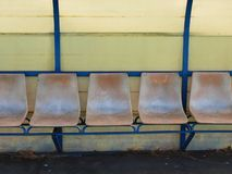 Old plastic seats on outdoor stadium players bench, chairs with worn paint Royalty Free Stock Photo