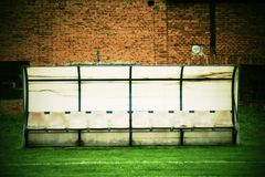 Old plastic seats on outdoor stadium players bench, chairs with worn paint below yellow roof. Royalty Free Stock Photos