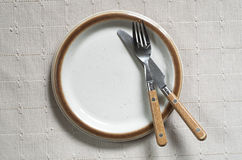 Old plate with fork and knife Stock Photos