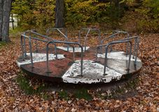 Old playground merry go round covered with fall leaves. Rusted merry go round in a wooded park Royalty Free Stock Images