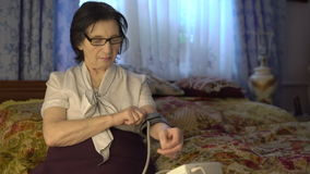 Old pleasant woman putting blood pressure measurement tool on hand. stock footage