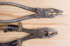 Old pliers. Two old hardly used pliers on wooden surface Royalty Free Stock Photography