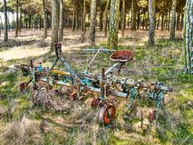 Old plow. Machinery plow into disuse.  Stands out the blue and red colors that still retains Royalty Free Stock Images