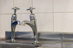 Old plumbing. Badly fitted sink taps with limescale. Selective f royalty free stock image