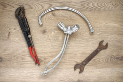 Old plumbing tools and tap on wooden background Royalty Free Stock Photo