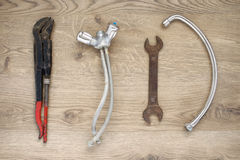 Old plumbing tools and tap on wooden background Stock Images