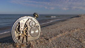 Old pocket clock on ocean beach stock footage