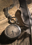 Old pocket watch. On a wooden board with the ancient newspaper and a feather stock image