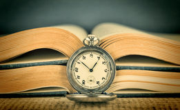 Old pocket watch and book Stock Photography