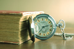 Old pocket watch. With old book in vintage picture style Stock Image