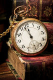 Old pocket watch and books in Low-key. Antique pocket clock showing a few minutes to midnight over ancient books in Low-key. Concept of time,the past or deadline Stock Images