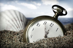 Old pocket watch buried in sand Royalty Free Stock Photo