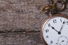 Old pocket watch on a chain on an old wooden table Stock Image