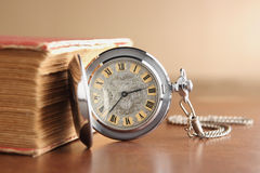 Old pocket watch. Close up of old pocket watch with old book Royalty Free Stock Photo