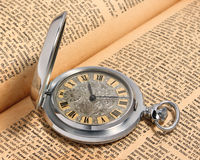 Old pocket watch on dictionary Stock Photos
