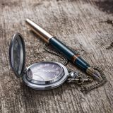 Old pocket watch and fountain pen on wood background Royalty Free Stock Images